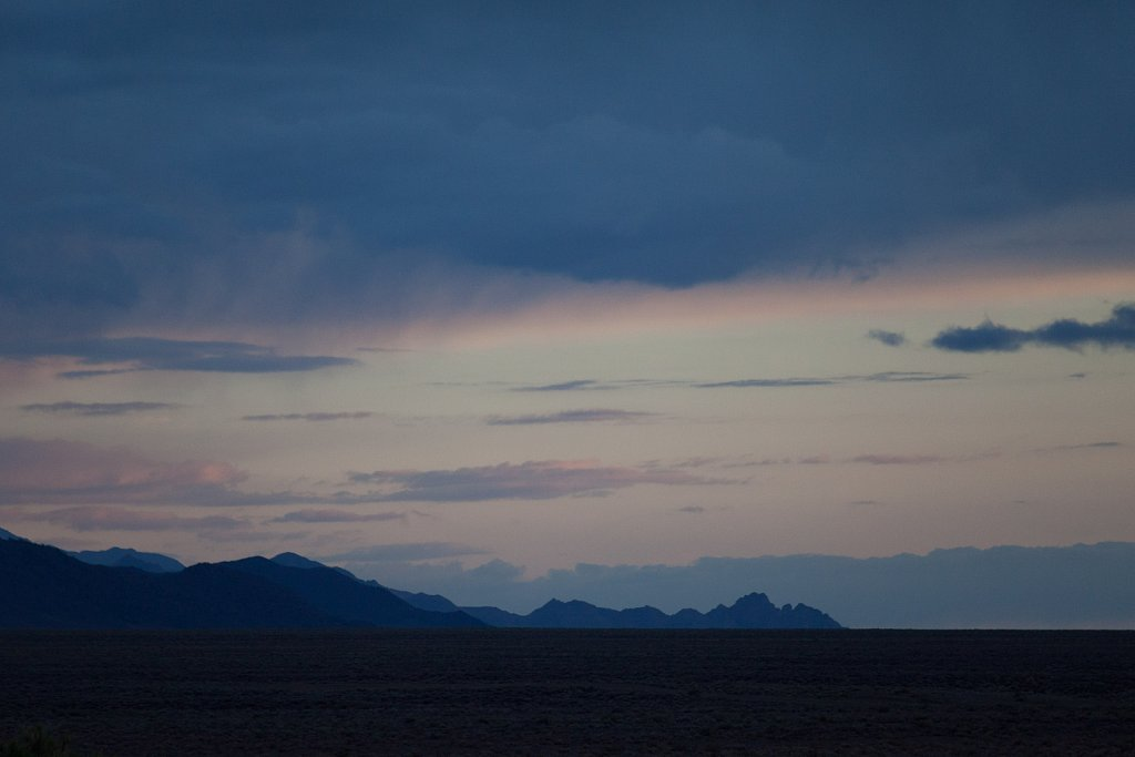 Dusk and a stray storm over jagged mountains in Nevada