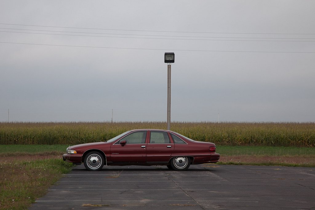 Maroon Chevy Caprice Classic in front of a corn field in Kansas