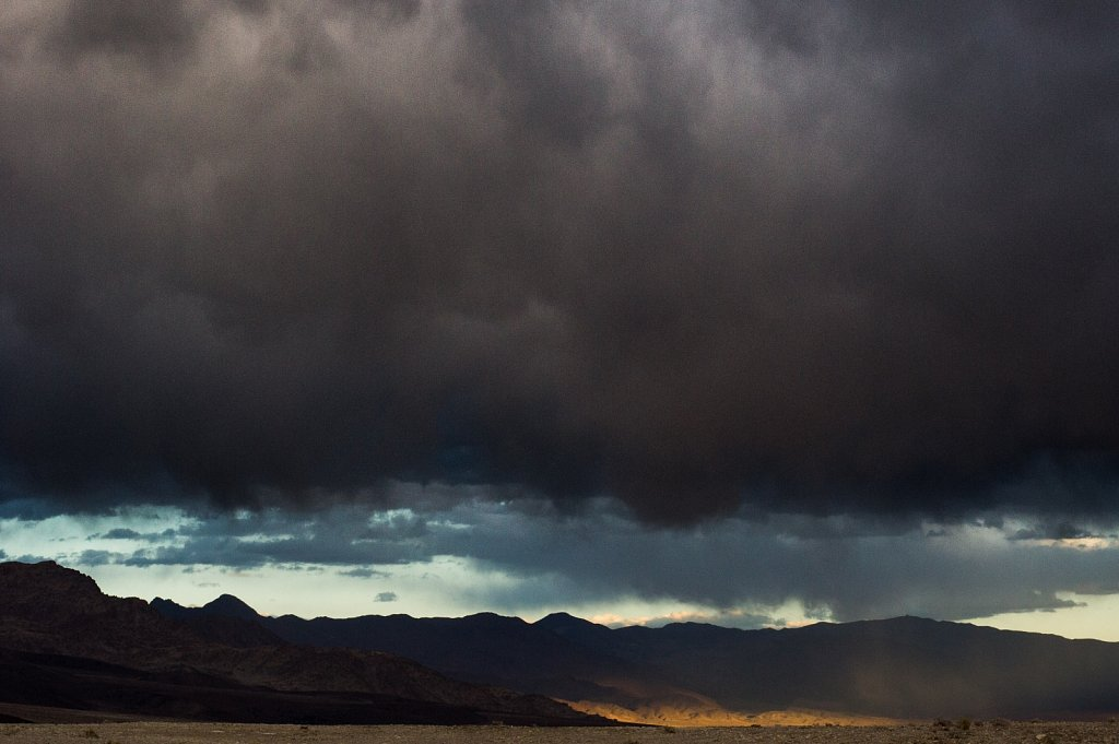 Heavy black clouds over sun dappled desert mountains