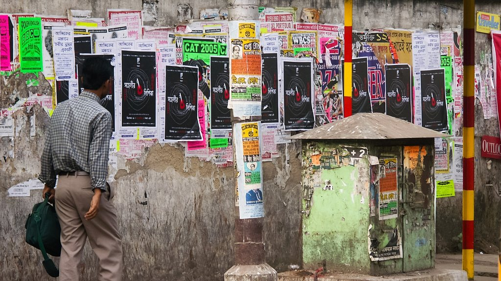 Man walking in front of posters in Kolkata