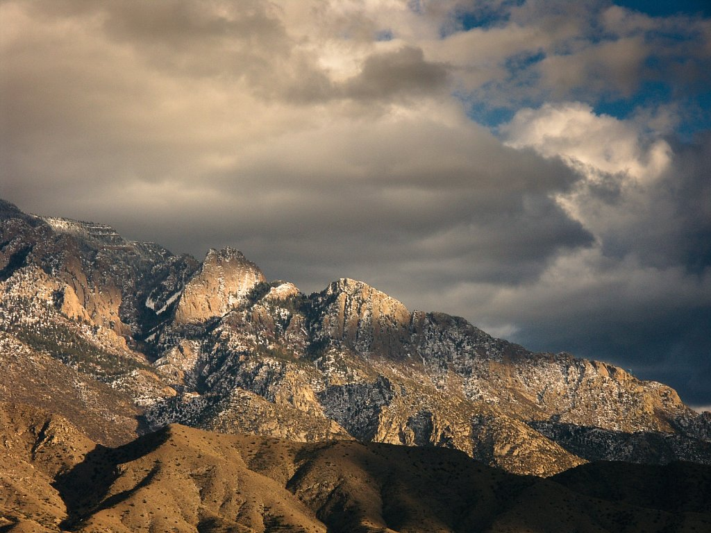 Telephoto shot of Sandia Mountain crest dusted with white and da