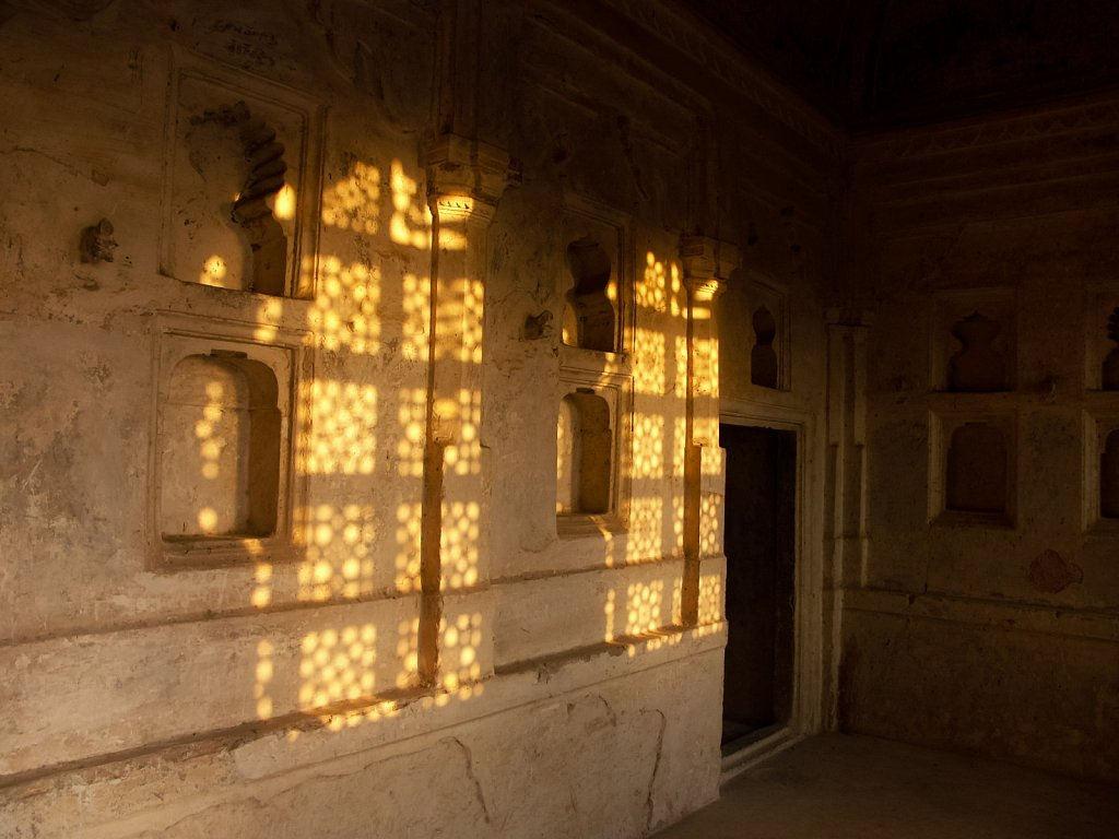 Late afternoon sun dapples the wall of an old castle in India