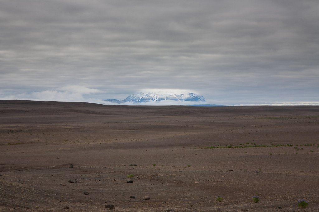 Flat topped snowcapped mountain over almost totally barren brown