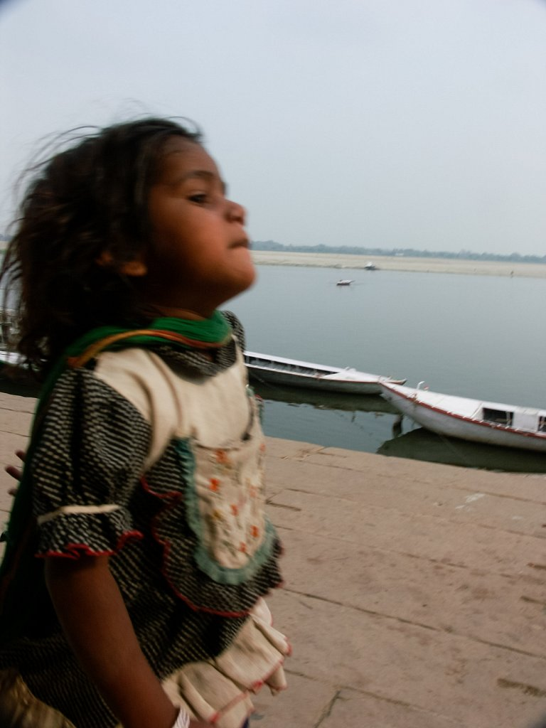Little girl running along the waterfron in Varanasi