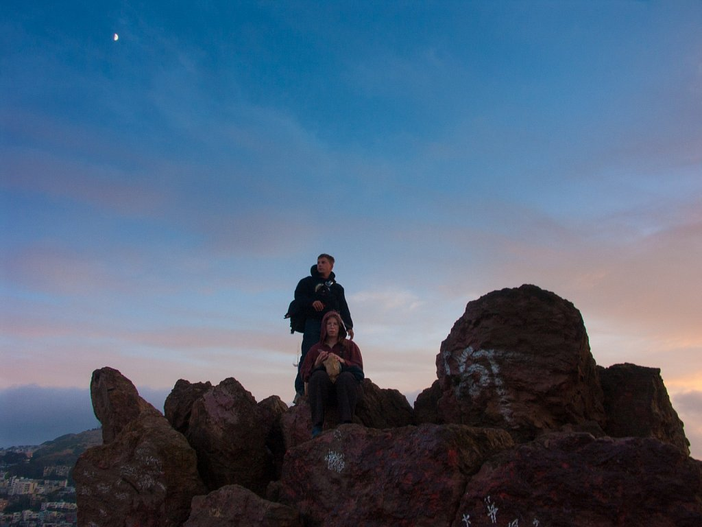 James and Kat atop Corona Heights with a half moon at sunset