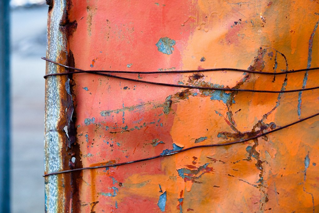 Closeup of wire wrapped around a pink and orange painted, rusted