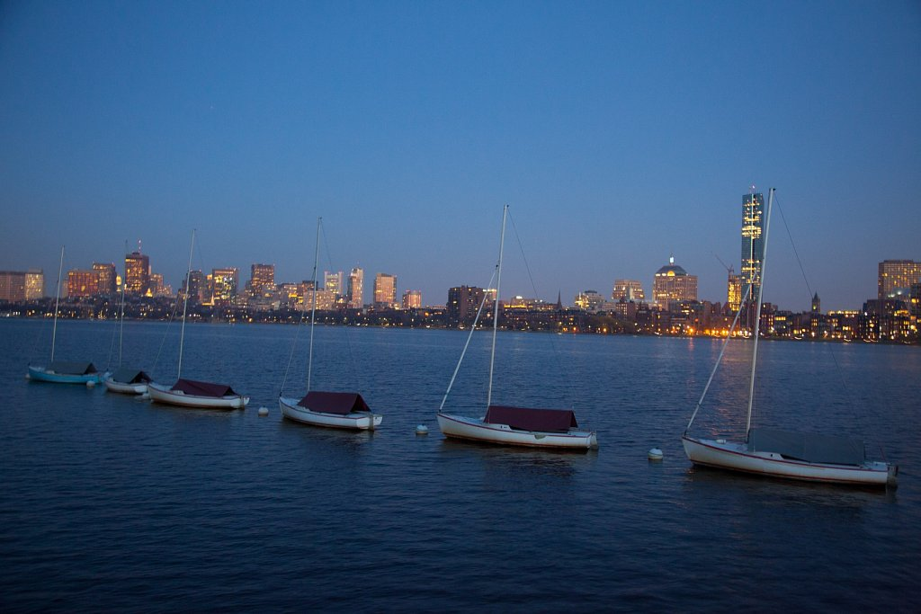 Boats lined up on the Charles River at Dusk with the Boston skyl
