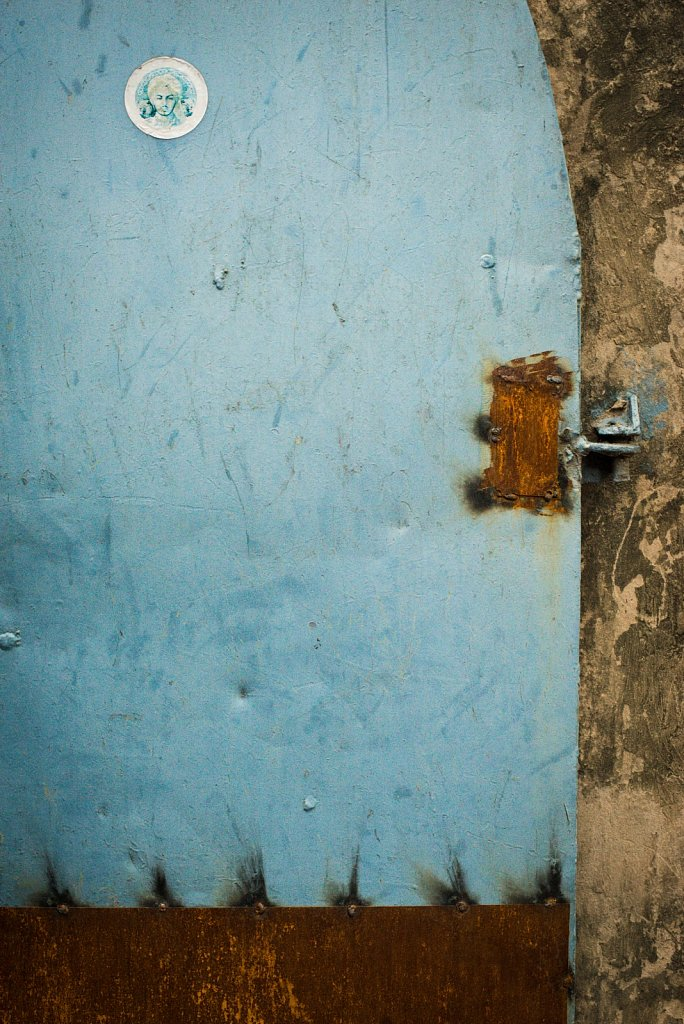 Blue door with rust and sticker in the rock garden of nek chand